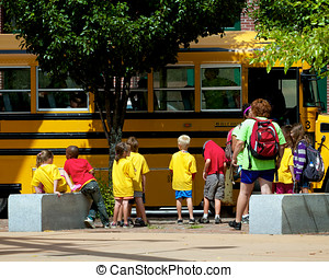 Kids and School Bus - A group of boys and girls getting on a...