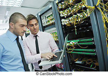 it engineers in network server room - group of young...