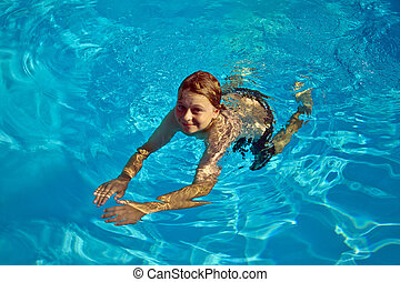 child swims in the pool  - child enjoys swimming in the pool