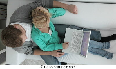 Couple at computer - Amorous couple sitting on sofa and...
