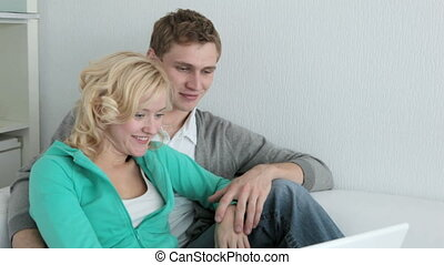 At laptop together - Amorous couple working with laptop at...