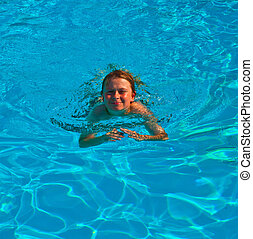 child swims in the pool and has fun - smiling child has fun...