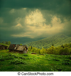 Mystery mountain landscape. Ray of light in dark clouds over...