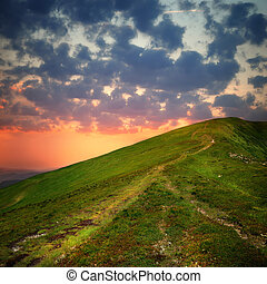 hill with pathway and clouds on sky in sunset time
