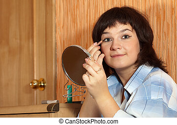 woman putting make up - young woman putting make up on her...