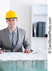 Close up of smiling architect working on a plan