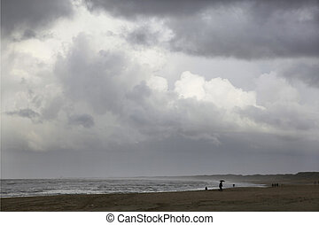 walking on a rainy beach under a dramatic cloudy sky