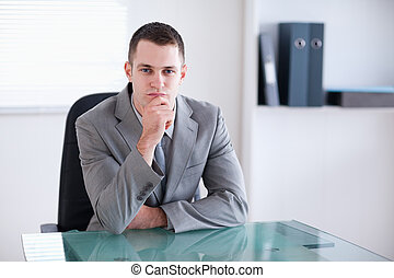 Thinking businessman sitting behind a table