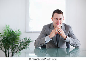 Young businessman getting good news sitting behind a table