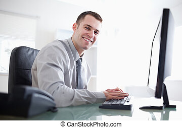 Businessman working with his computer - Smiling businessman...
