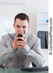 Businessman getting a pleasant text message on his chellphone
