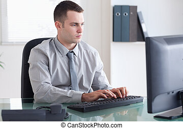Businessman typing on his computer - Young businessman...