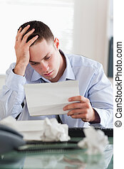 Businessman reading a bill - Frustrated businessman reading...