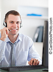 Close up of smiling call center agent speaking with costumer...