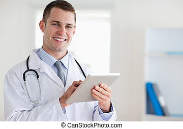 Smiling doctor with his tablet