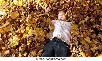 Amusing kid - The boy abruptly buried in autumn leaves