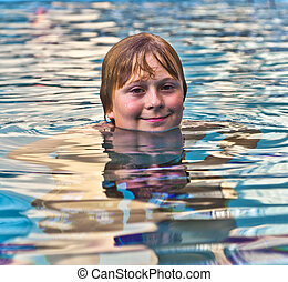 boy enjoys swimming in an outdoor pool