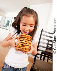 Young Girl Eating Stack of Cookies