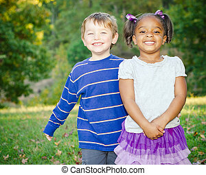 Two children playing in park - Young African-American girl...
