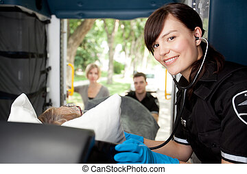 Paramedic in Ambulance with Patient - Portrait of a...