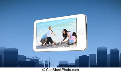 Smartphone showing a family building a sandcastle on the...