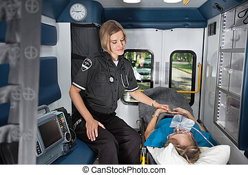 Senior Care in Ambulance - Female EMT worker showing care to...