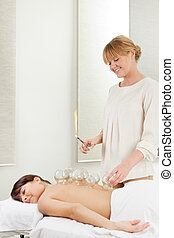 Fire Cupping - Young relaxed woman receiving fire cupping...