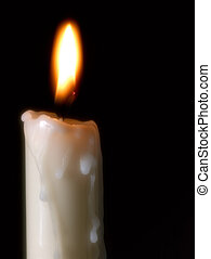 burning candle over black background with focus on fire and...