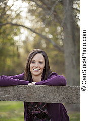 Young Woman by Fence - Pretty young woman leans against a...