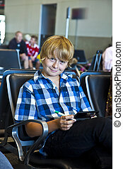 boy is waiting for departure at the airport and playing an...