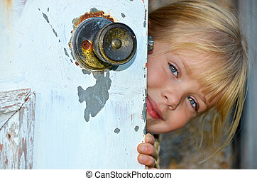 girl peeking around door - Little girl peeking around a...