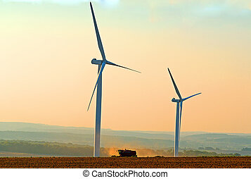 a combine harvester between two wind turbines