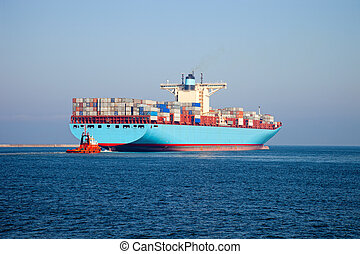 Container ship leaves the port, assist by a tugboat. - One...