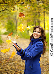 Girl throw up maple leaves - Girl in blue coat throw up...