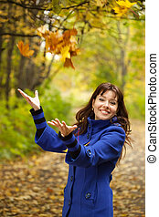 Girl throw up yellow leaves - Girl in blue coat throw up...