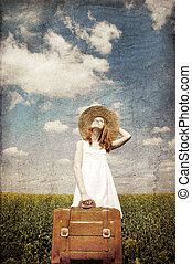Lonely girl with suitcase at country. Photo in old color...