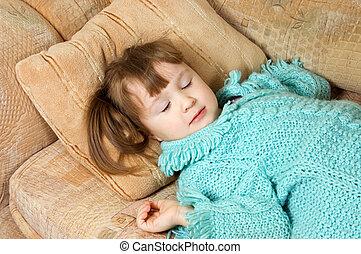 Little girl sleeps on a sofa