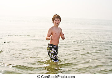 young boy in the sea in cold water but showing all right,...