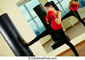 Kick boxing - Portrait of young woman in red boxing gloves...