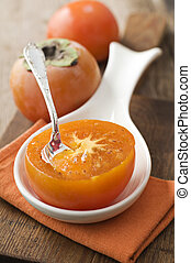 Persimmon - Slice persimmon with spoon close up shoot