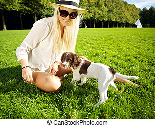 Playtime Dog And Woman In Park - A stylish young blonde...
