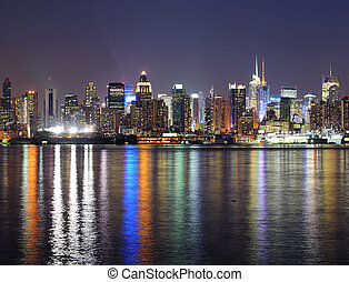 New York City Manhattan midtown skyline at night with lights...