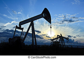 pump-jack group - oil pumps on the sunset sky background