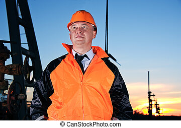 Engineer in an Oil field - Oil worker in orange uniform and...