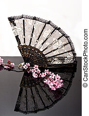 Chinese fan on black shiny surface with pink blossoms