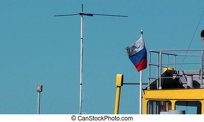 Russian flag moving at the wind on tugboat.
