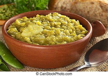 Split pea soup with potato in rustic bowl