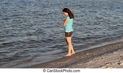 Moody Woman Walking Beach - Woman walks along the shoreline...