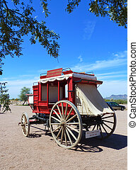 red wooden stagecoach i n open area without horses