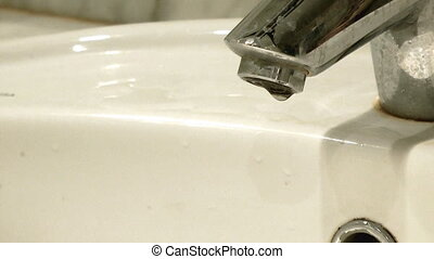 Leaky faucet - Flowing water in washbowl. Leaky faucet.